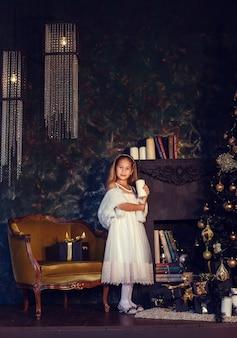 Ein kleines mädchen mit braunen haaren auf einem dunklen hintergrund im niedlichen kleid. gold und schwarz. weihnachtsbaum- und neujahrsdekorationen