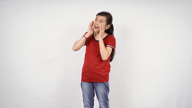 Ein kleines mädchen mit den händen, die nahe ihrem mund und den händen zum mund gehalten werden. isolierter weißer hintergrund. ankündigung, aufmerksamkeitskonzept