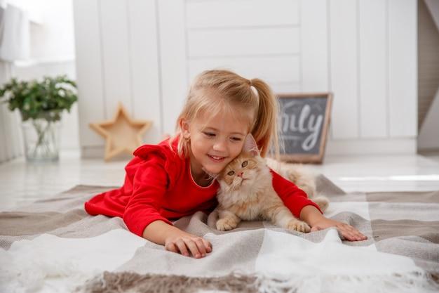 Ein kleines mädchen mit einem mankun kätzchen, das auf dem boden des hauses liegt. das konzept einer menschlichen familie und eines haustieres