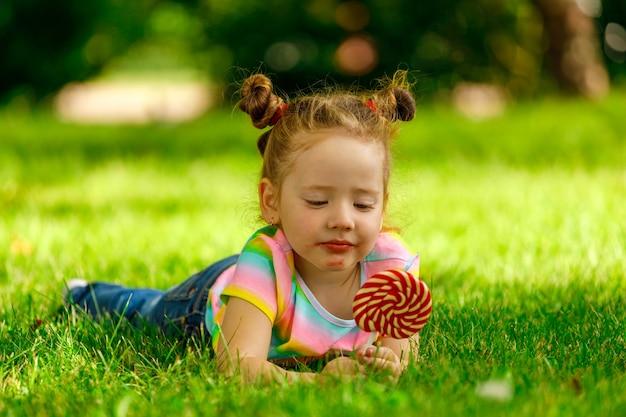 Ein kleines mädchen mit einem roten lutscher liegt auf dem sommergras im park.