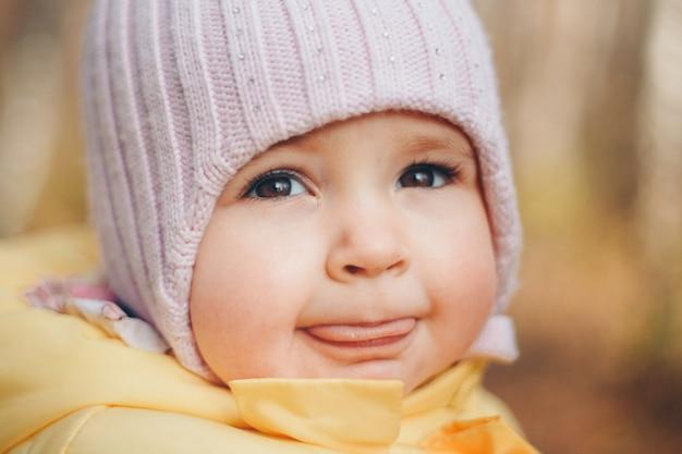 Ein kleines mädchen mit einem warmen hut auf dem kopf lächelte. kindheit, gesundheit, ivf, kalte zeit