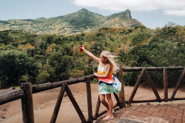 Ein kleines mädchen mit einer roten dose getränk in ihren händen vor dem hintergrund der berge der insel mauritius, naturschutzgebiet, chamarel sands.mauritius insel.