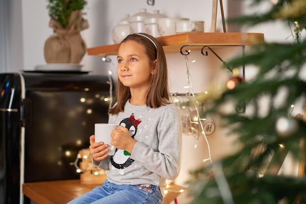 Ein kleines mädchen mit einer tasse heißen tees träumt von einem weihnachtsgeschenk für weihnachten