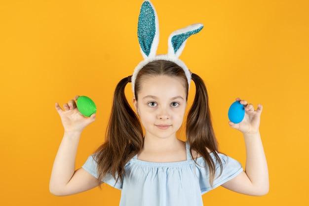 Ein kleines mädchen mit hasenohren auf dem kopf hält zwei blaue und grüne eier in den händen