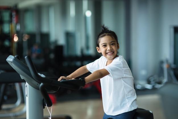 Ein kleines mädchen mit heimtrainer im fitnessstudio. fitness-frau mit luftfahrrad im fitnessstudio.