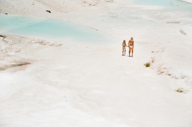Ein kleines mädchen mit ihrer mutter in badeanzügen und sonnenbrille auf einem weißen berg, eine familie an einem sonnigen sommertag auf einem anderen planeten, pamukkale, türkei