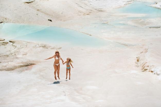 Ein kleines mädchen mit ihrer mutter in badeanzügen und sonnenbrille auf einem weißen berg