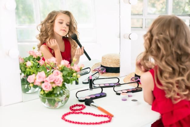 Ein kleines mädchen mit kosmetik, das nahe dem spiegel sitzt.