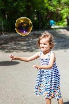 Ein kleines mädchen mit kurzen haaren und in einem kleid spielt im sommer im park, fängt seifenblasen, lacht, emotionen, kindheit, plaudert mit freunden