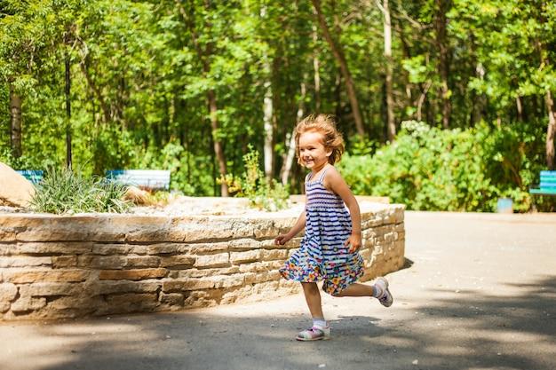 Ein kleines mädchen mit kurzen haaren und in einem kleid spielt im sommer im park, fängt seifenblasen, lacht, emotionen, kindheit.