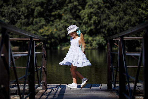 Ein kleines mädchen mit langen haaren in einem weißen kleid steht am ufer des flusses. spaziergang am see an einem sonnigen sommertag