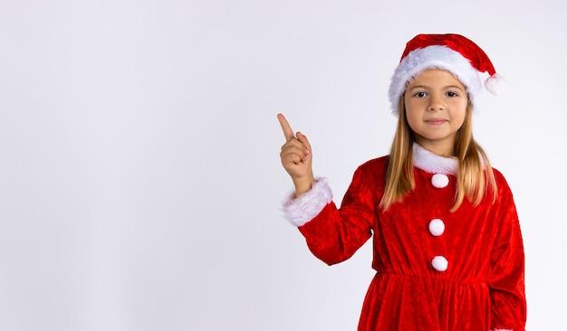 Ein kleines mädchen mit langen haaren und verkleidet wie der weihnachtsmann aussieht