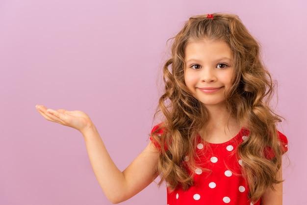 Ein kleines mädchen mit lockigem haar und ihrer hand zur seite auf rosa hintergrund