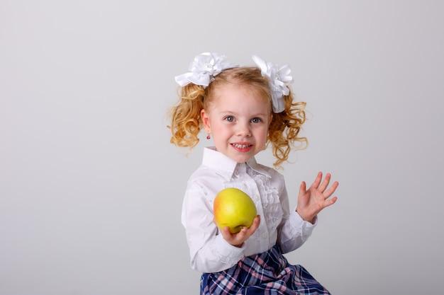 Ein kleines mädchen mit lockigen haaren, ein blondes schulmädchen in schuluniform, das einen apfel in den händen hält und auf einem weißen raum lächelt