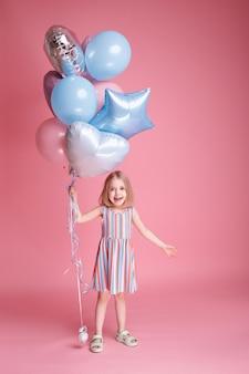 Ein kleines mädchen mit luftballons spielen. kindertag