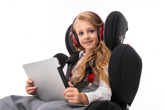 Ein kleines mädchen mit make-up und dem langen blonden haar, die in einem autobabystuhl mit tablette, kopfhörern sitzen, hören musik und plaudern mit freunden