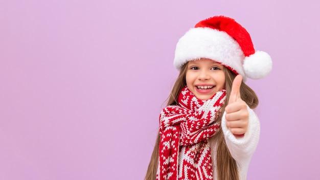 Ein kleines mädchen mit neujahrsmütze und warmem schal freut sich sehr und zeigt den daumen nach oben. ein kind in einem weihnachtskostüm auf einem isolierten hintergrund.