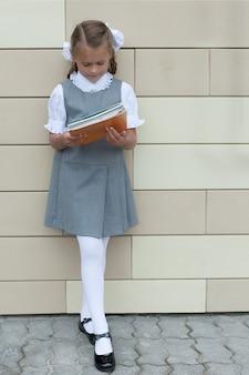 Ein kleines mädchen mit notizbüchern und einem rucksack steht in der nähe der schule