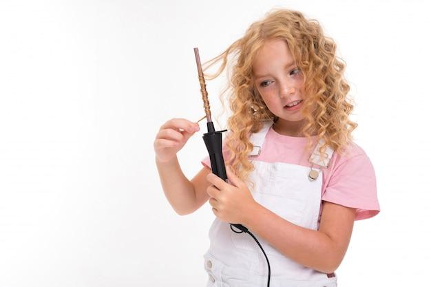 Ein kleines mädchen mit rotem haufenhaar in einem trikot, weißem overall und weißen turnschuhen spinnt ihr haar auf einem dünnen pflug.