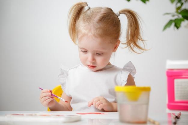 Ein kleines mädchen, mit schwänzen auf dem kopf, zeichnet aquarelle, die an einem tisch sitzen. das kind mag es, kreativ zu sein