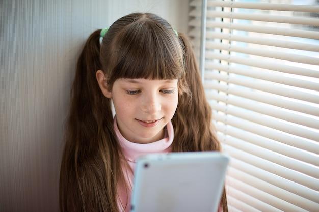Ein kleines mädchen mit sommersprossen und blauen augen, die am fenster sitzen und eine tablette verwenden