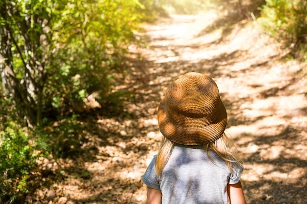 Ein kleines mädchen mit strohhut geht einen weg im wald entlang