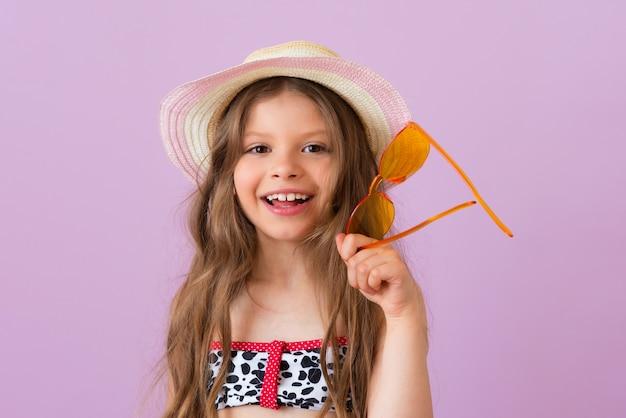 Ein kleines mädchen mit strohhut hält ihre brille und lächelt.