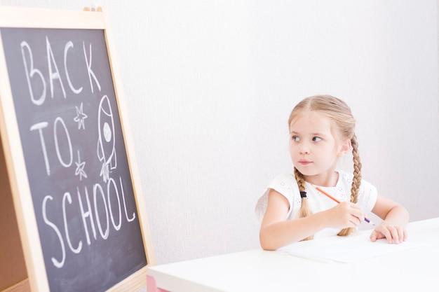 Ein kleines mädchen mit zöpfen sitzt an einem schreibtisch und hebt die hand. zurück zur schule. zuhause unterrichtet
