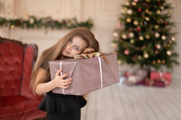 Ein kleines mädchen öffnet ein weihnachtsgeschenk vom weihnachtsmann. weihnachtsgeschichte. glückliche kindheit.