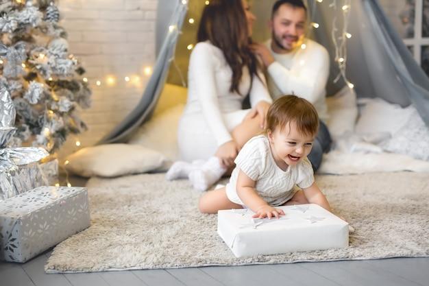 Ein kleines mädchen öffnet heimlich ihr weihnachtsgeschenk von ihren eltern