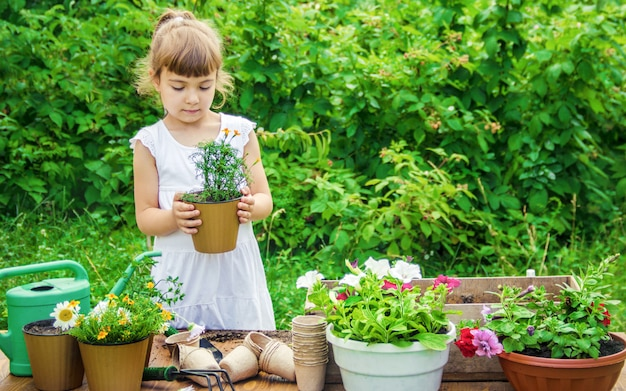 Ein kleines mädchen pflanzt blumen. der junge gärtner selektiver fokus
