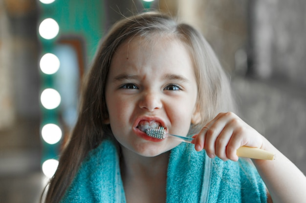 Ein kleines mädchen putzt sich im badezimmer die zähne. porträt eines kindes mit einer zahnbürste
