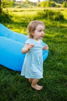 Ein kleines mädchen ruht und spielt an der frischen luft. auf einer blauen aufblasbaren matratze herumalbern