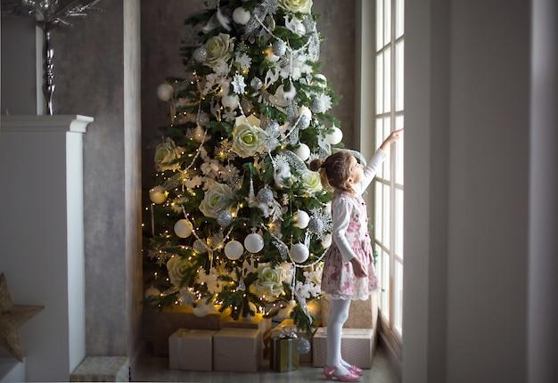 Ein kleines mädchen schaut aus einem großen fenster in der nähe eines weihnachtsbaumes. warten auf ein wunder, weihnachtliches weißes dekor im wohnzimmer des hauses. neues jahr, märchen und magie, kinderträume