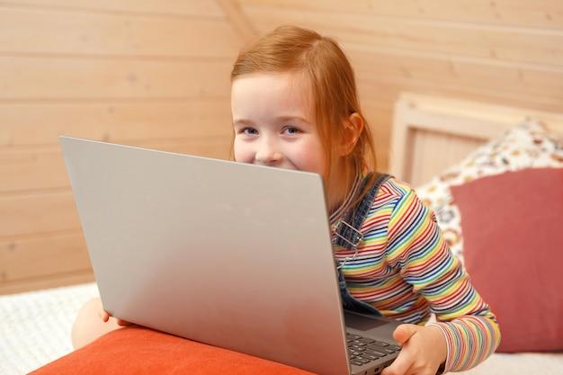 Ein kleines mädchen schaut mit verschiedenen emotionen auf den computer. mädchen spielt auf einem computer