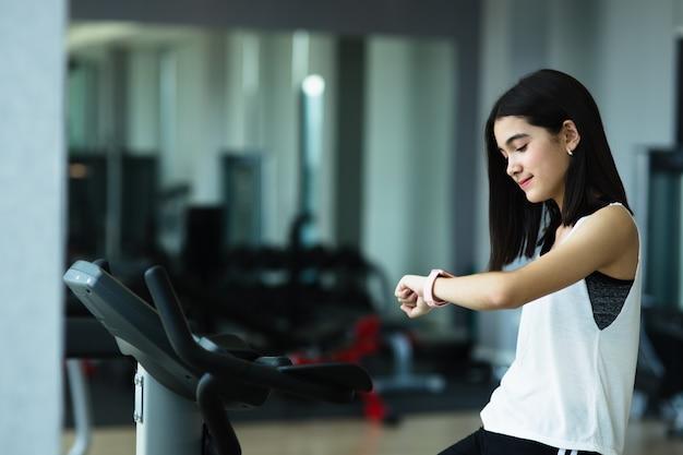 Ein kleines mädchen schaut nach dem training im fitnessstudio auf eine intelligente uhr. gesundes konzept. die frau überprüft nach dem training die ergebnisse auf der uhr. das sportkonzept der kinder