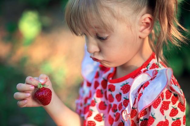 Ein kleines mädchen schaut überrascht auf eine erdbeere in ihren händen. das kind macht gesichter