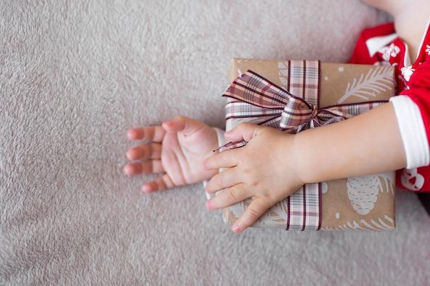 Ein kleines mädchen schläft auf einem bett in einem weihnachtsmannkostüm und umarmt ein weihnachtsgeschenk.