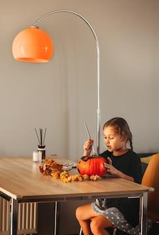 Ein kleines mädchen schmückt einen kürbis in einem raum zu halloween. kinder dekorieren zu hause. kinder schnitzen kürbis. gruseliger halloween-spaß