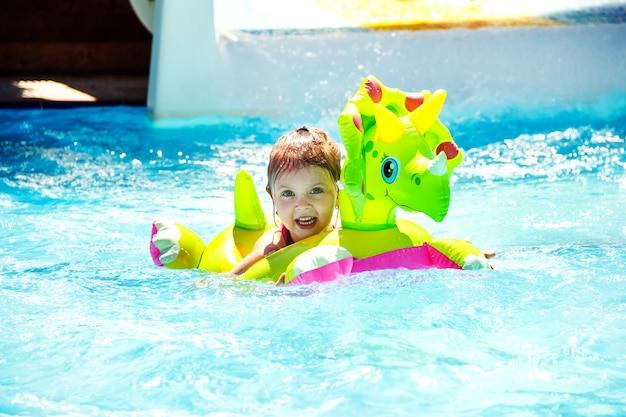 Ein kleines mädchen schwimmt im sommer im urlaub in einem aufblasbaren kreis im pool