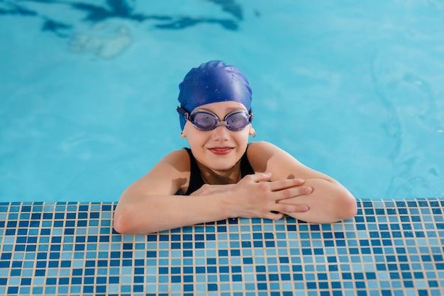 Ein kleines mädchen schwimmt und lächelt im pool. gesunder lebensstil.