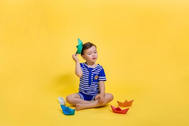 Ein kleines mädchen seemann mit einem papierboot in den händen sitzt auf einem gelben platz. ein schönes mädchen in einem matrosenanzug schaut weg. origami aus papier.