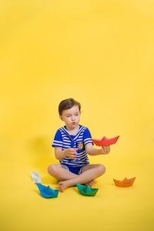 Ein kleines mädchen seemann mit papierbooten, die auf einem gelben raum sitzen. ein schönes mädchen mit einem pferdeschwanz in einem seemannskleid spielt mit bunten papierbooten. origami aus papier.