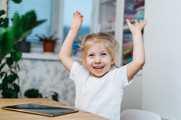 Ein kleines mädchen sitzt an einem tisch mit einer tablette, die hände in die luft erhoben, lächelnd und glücklich, glück erfahren.