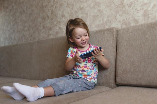Ein kleines mädchen sitzt auf der couch und schaut auf das telefon