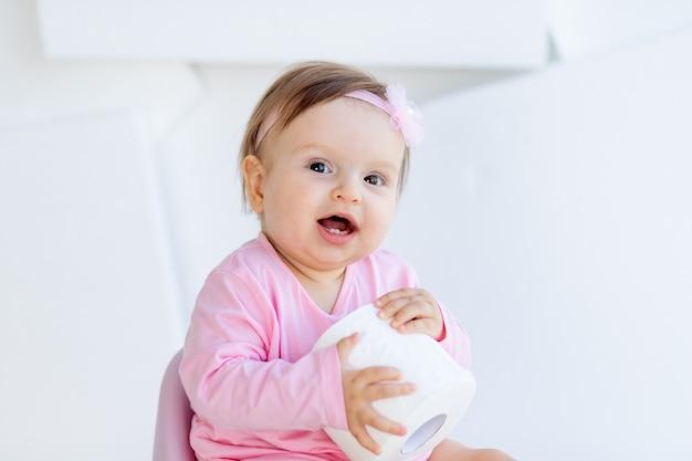 Ein kleines mädchen sitzt auf einem töpfchen in rosa kleidern in einem hellen raum und spielt mit toilettenpapier
