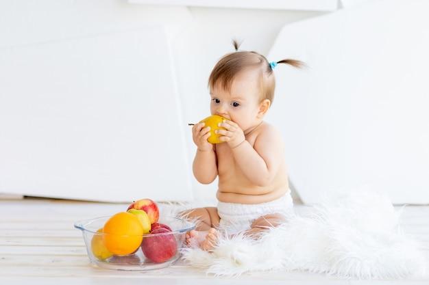 Ein kleines mädchen sitzt in einem hellen raum mit einem obstteller und isst eine birne