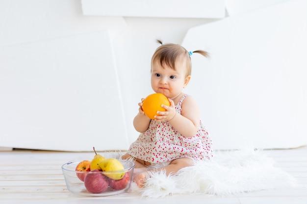 Ein kleines mädchen sitzt in einem hellen raum mit einem obstteller und isst eine orange