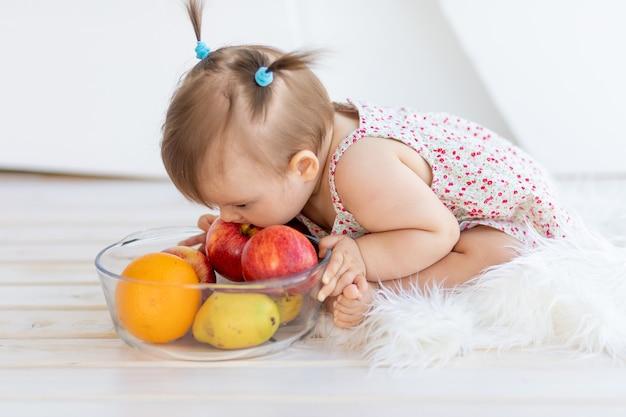 Ein kleines mädchen sitzt in einem hellen raum mit einem obstteller und isst einen apfel