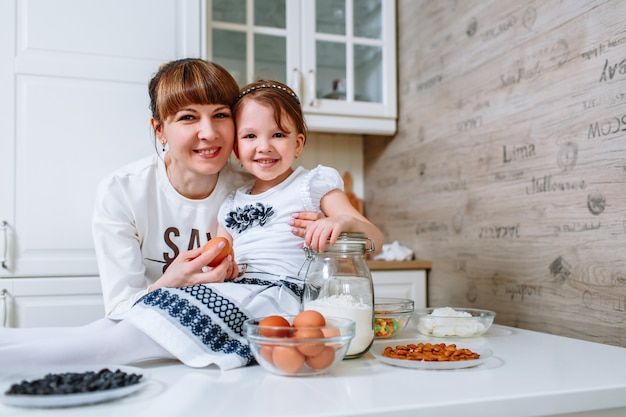 Ein kleines mädchen sitzt lächelnd auf dem küchentisch und ihre mutter steht neben ihr
